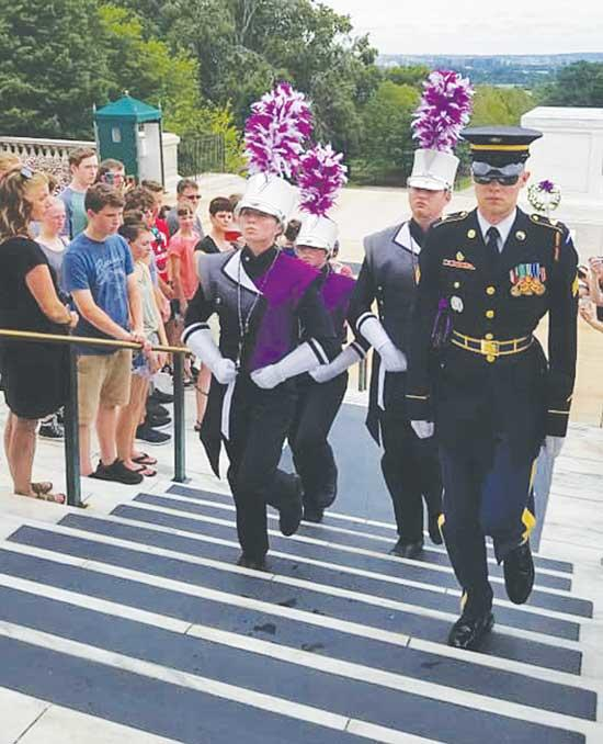 Buffalo High School Drum Majors from The HERD Marching Band return to their post after the placement of a purple wreath on the Tomb of the Unknown Solider at Arlington National Cemetery in Virginia on Sunday, July 7. Pictured walking up the steps...